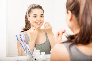 Junge Frau die Zahnseide verwendet um Mundgeruch vorzubeugen